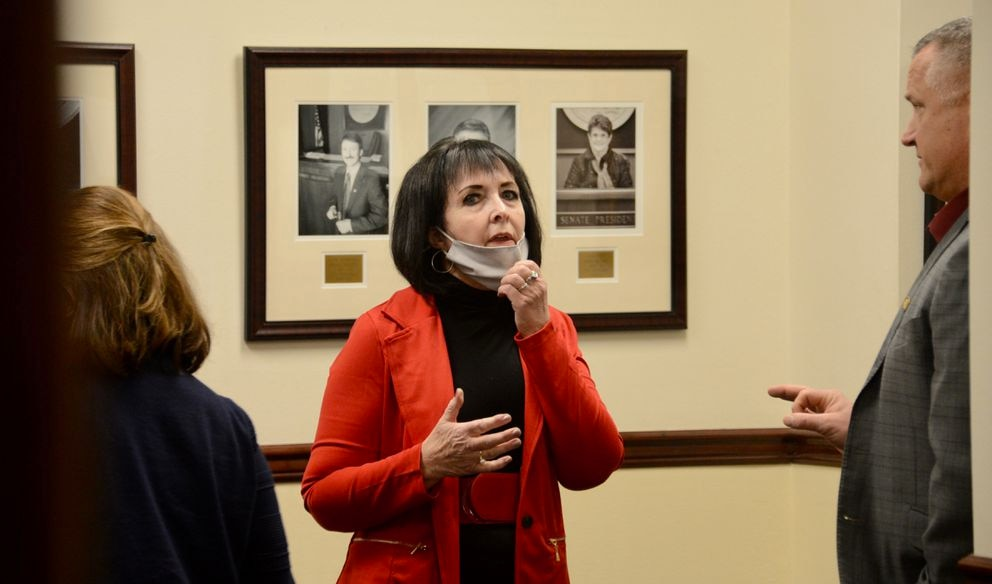 Sen. Shelley Hughes, R-Palmer, puts on a face mask while talking about COVID-19 rules in the state Capitol with Sen. Mike Shower, R-Wasilla (right) and Sen. Lora Reinbold, R-Eagle River (left, facing away from camera). Reinbold, chair of the Senate Judiciary Committee, incorrectly said Wednesday, Feb. 3, 2021 that committee chairs may set mask rules in the state Capitol. Everyone who enters the Capitol is required to wear a mask unless the rules are changed by joint action from the Senate President and Speaker of the House. (James Brooks / ADN)