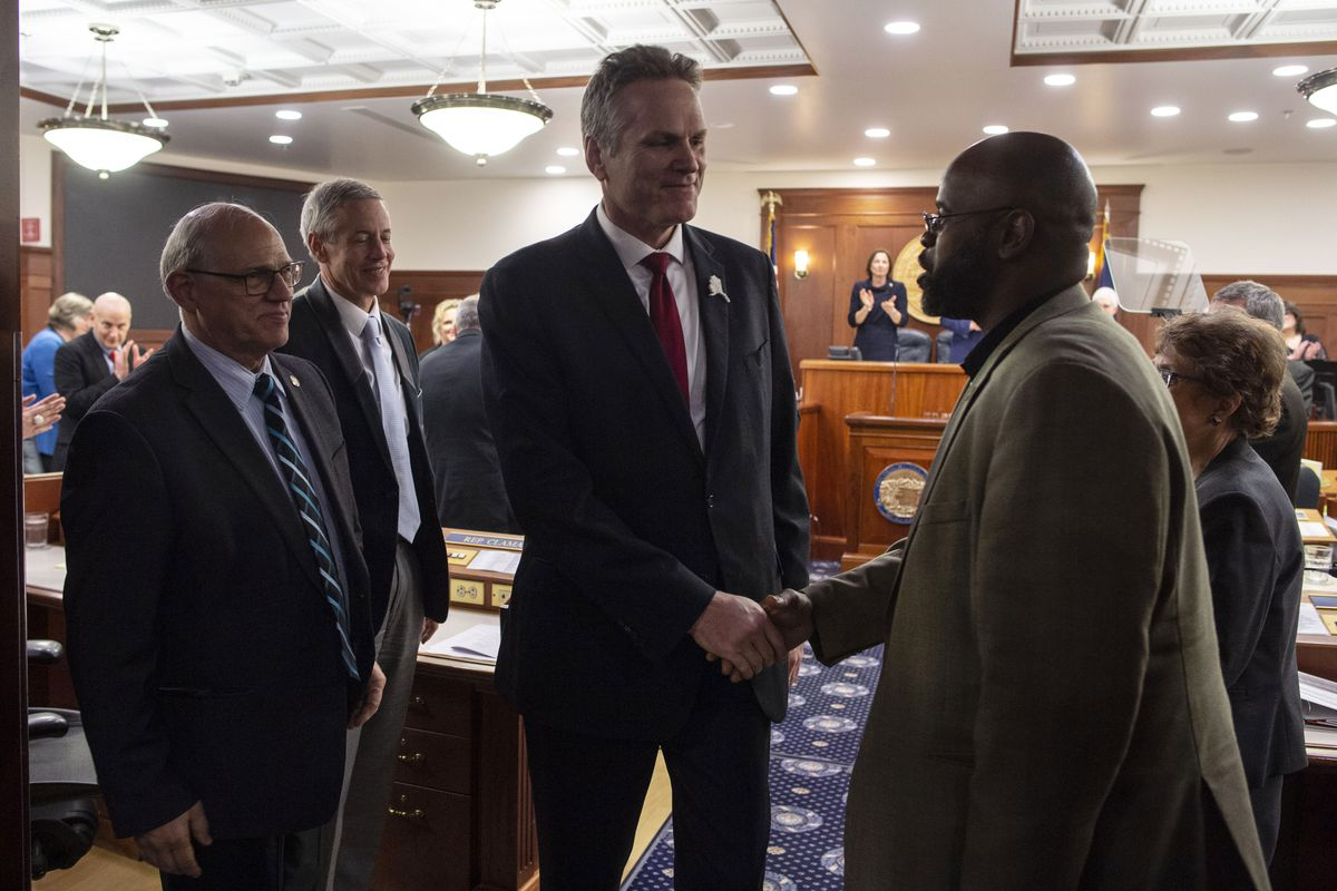Gov. Mike Dunleavy, center, shakes hands with Sen. David Wilson, right, as he leaves the House chambers after delivering his State of the State speech to a Joint Session of the Alaska Legislature at the Alaska State Capitol in Juneau, Alaska, Monday, Jan. 27, 2020. (AP Photo/Michael Penn)