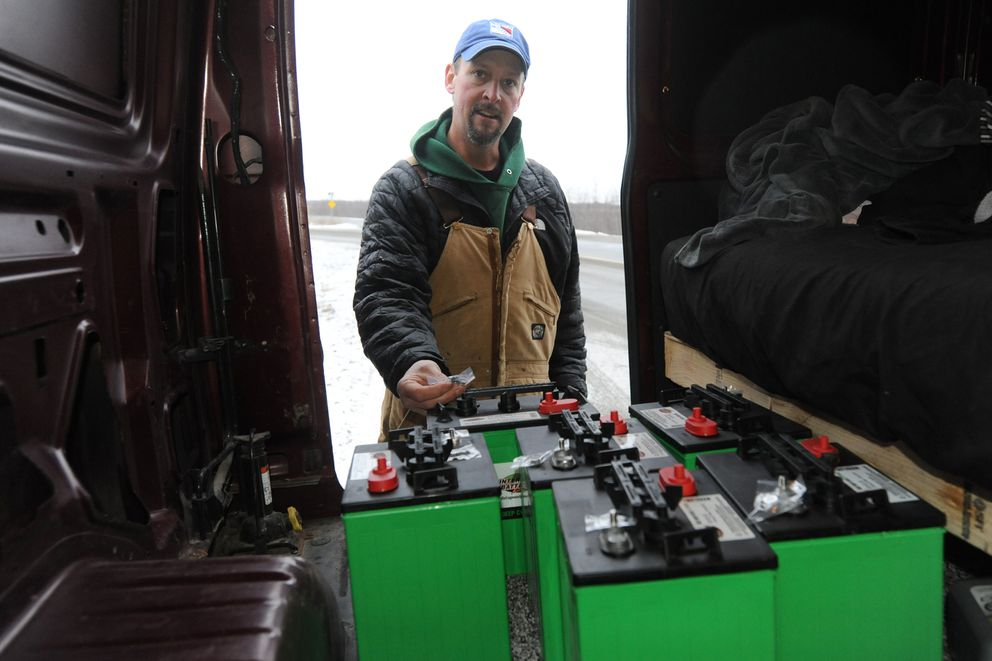 Jason Tolstrup uses 6-volt golf cart batteries to power the lights on the Christmas tree along the Glenn. (Bill Roth / ADN)