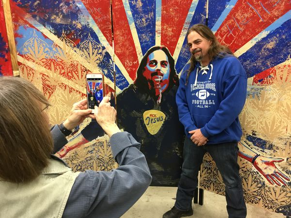 Mark Weaver poses with a mural made of him by UAA art students while one of the artists, Sharon Dale, takes a picture. Feb. 7, 2017. (Charles Wohlforth / ADN)