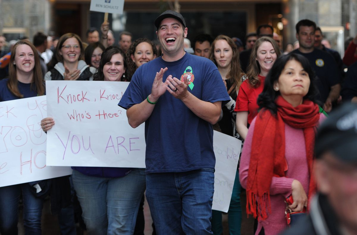 Anchorage firefighter/paramedic Ben Schultz reacts to family and friends gathered to welcome him home at the airport on Thursday, May 24, 2018, nearly a year after falling from a ladder during a training accident. (Bill Roth / ADN)