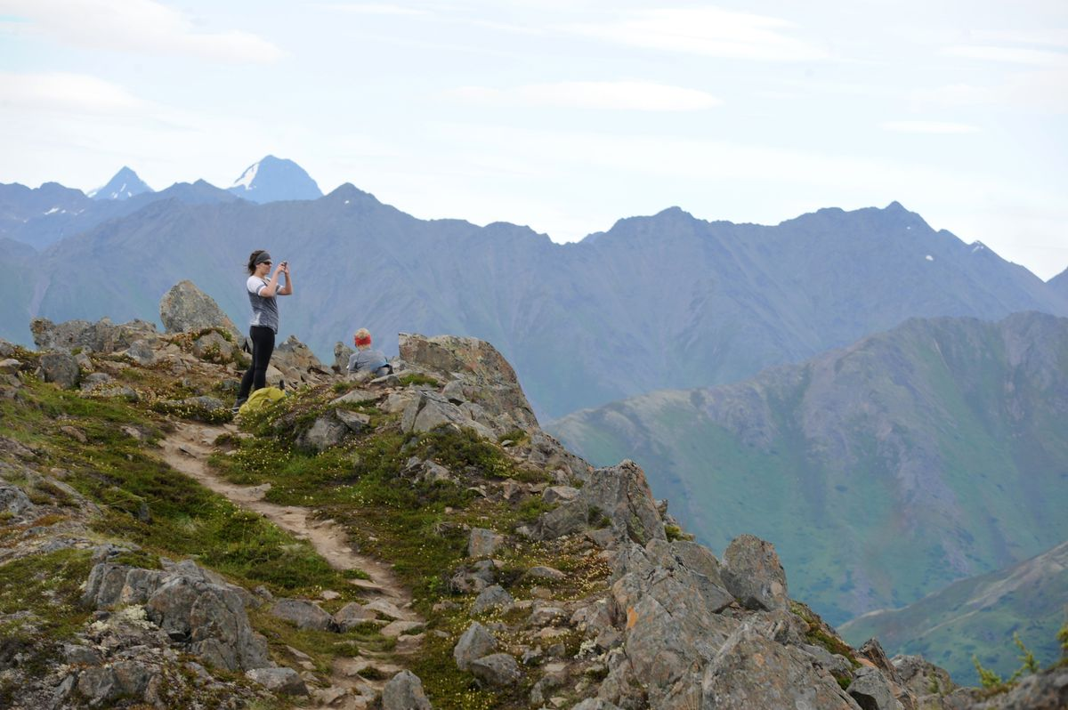 Hikers take a break and photograph the scenery at the top of the Bird Ridge hike. Ridges of Chugach Mountains are in the background. (Anne Raup / Alaska Dispatch News archive)