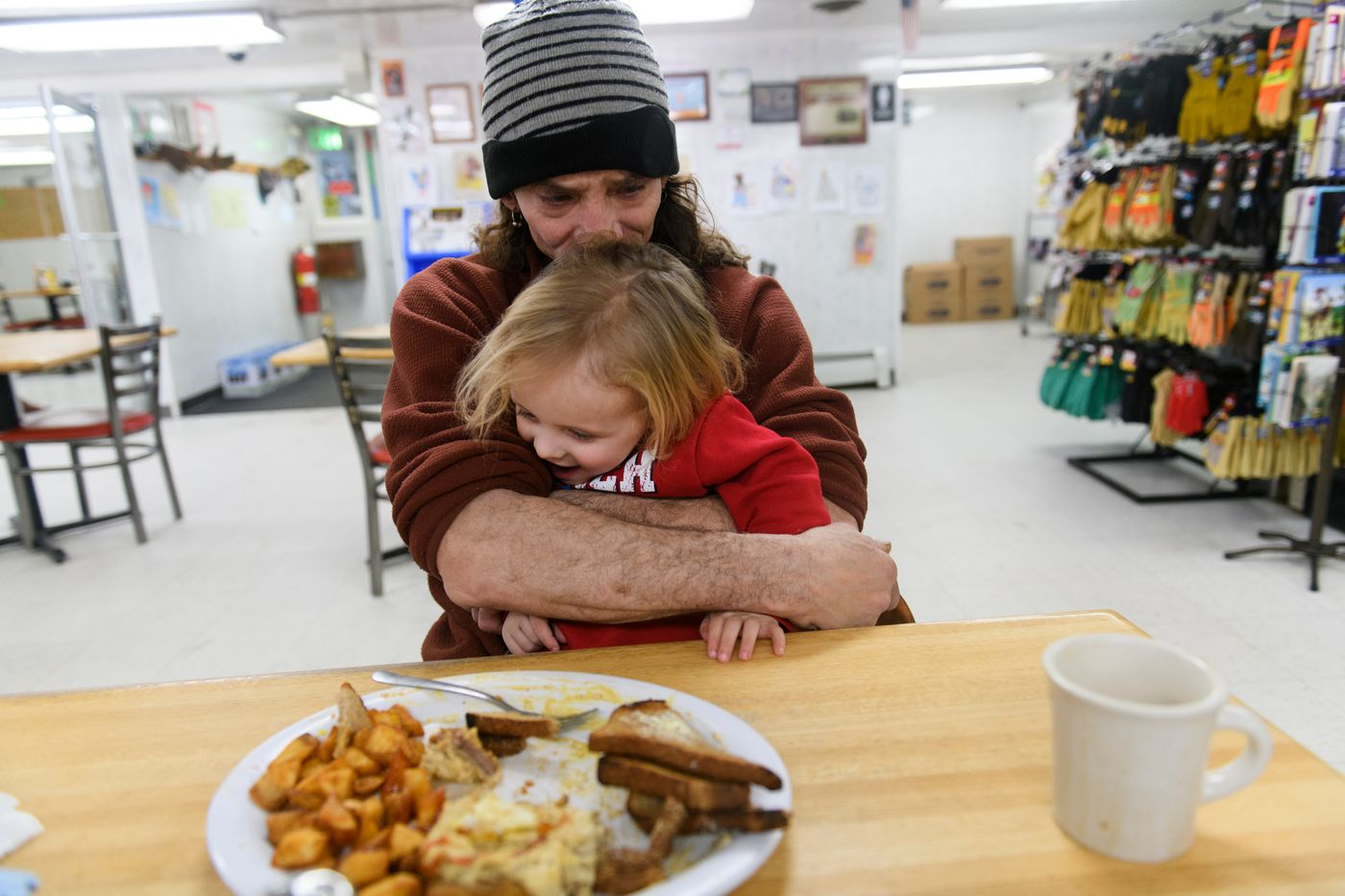 Lance Mackey holds his 2-year-old son Atigun during a stop for food at the Hilltop Truck Stop outside of Fairbanks. (Marc Lester / ADN)