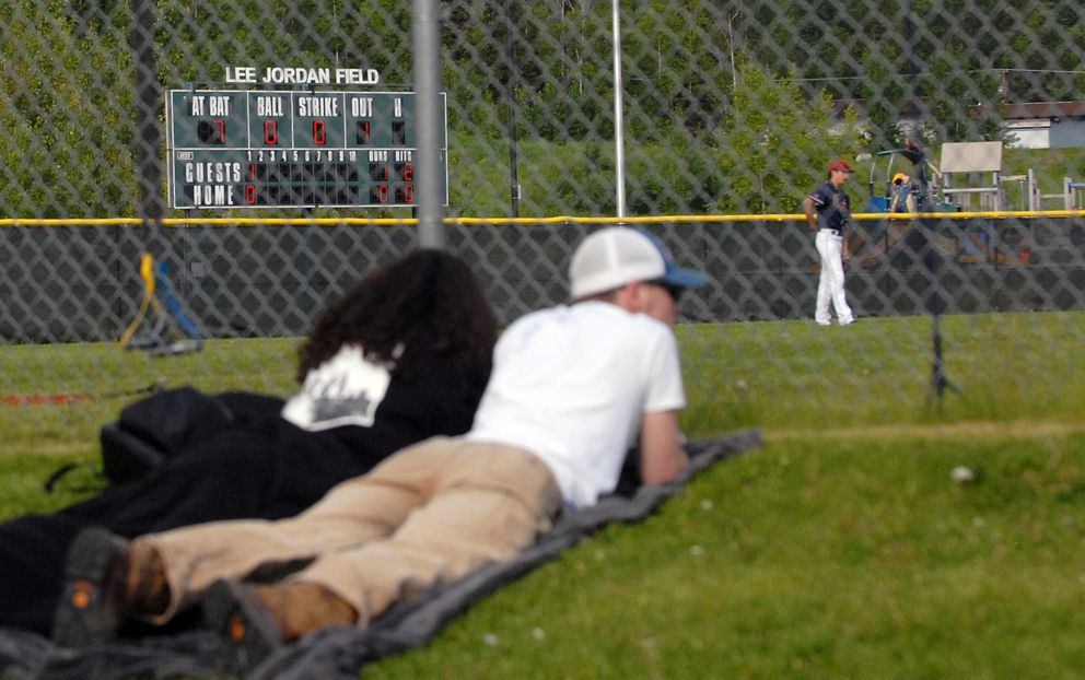 People catch the action from a hill behind the outfield fence. (Matt Tunseth / Chugiak-Eagle River Star)
