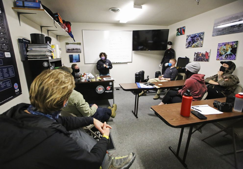 Melissa Flores takes notes while she and a group of freedivers, who dived in Rabbit Lake the weekend prior, work on a video of the trip from Dive Alaska in Anchorage on Sunday, Jan. 10, 2021. (Emily Mesner / ADN)