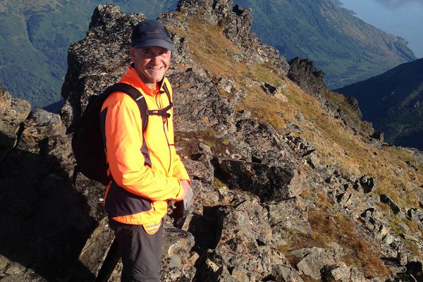 Steve Thompson smiles at the summit of North Suicide Peak on Saturday, Aug. 27, 2016. Bird Ridge and the waters of Turnagain Arm can be seen in the background. (Vicky Ho / Alaska Dispatch News)