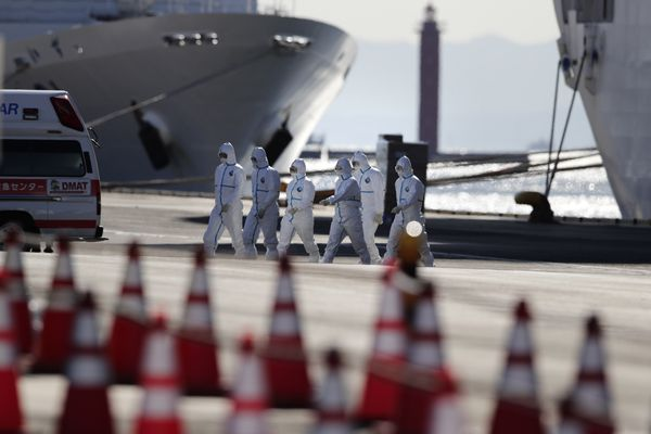 FILE - In this Feb. 11, 2020, file photo, medical workers with protective suites walk away from the quarantined Diamond Princess cruise ship in Yokohama, near Tokyo. Life on board the luxury cruise ship, which has dozens of cases of a new virus, can include fear, excitement and soul-crushing boredom, according to interviews by The Associated Press with passengers and a stream of tweets and YouTube videos. (AP Photo/Jae C. Hong, File)