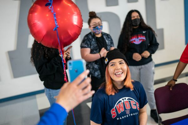 East High senior Kristi Anderson FaceTimes with a coach after signing a letter of intent to play basketball at Southwestern Oregon Community College, on Wednesday, April 14, 2021 at East High School in Anchorage. (Loren Holmes / ADN)