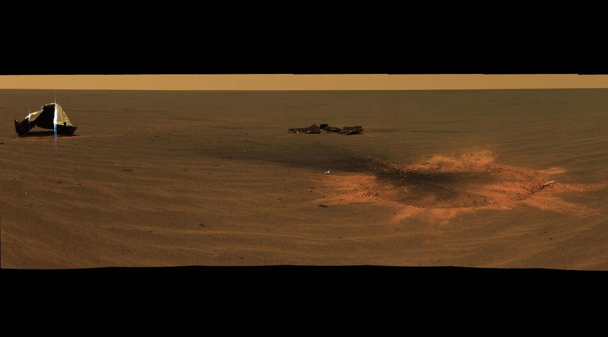 Opportunity's heat shield impact site is seen on Mars in an approximately true-color mosaic of panoramic camera images taken Dec. 28, 2004. On the left, the main heat shield piece is inverted and its metallic insulation layer glints in the sunlight. Handout courtesy of NASA/JPL/Cornell