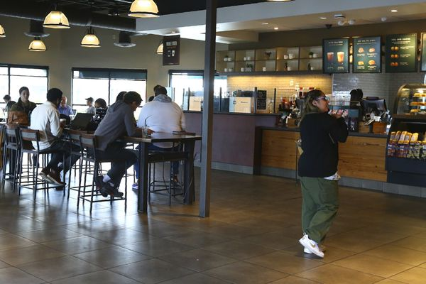This Wednesday, Jan. 15, 2020, photo, shows patrons at a local Starbucks Community Store, in Phoenix. The larger Starbucks location has a community meeting space for events and programming, and offers local community hiring. (AP Photo/Ross D. Franklin)