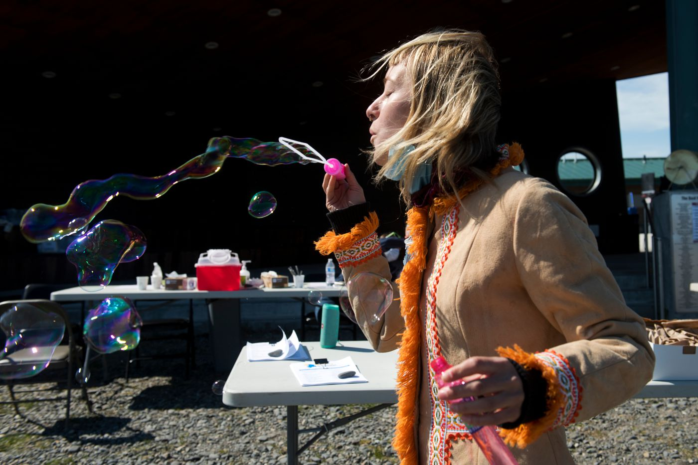 Nurse Annie Garay blows bubbles to attract attention to South Peninsula Hospital's pop-up COVID-19 vaccine clinic on the Homer Spit. (Marc Lester / ADN)