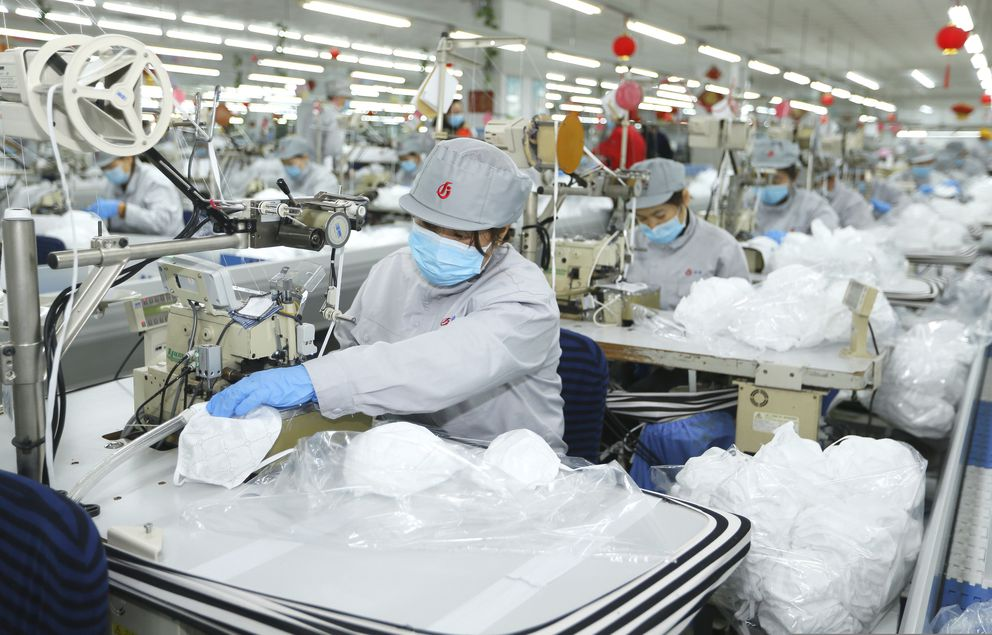 In this photo released by Xinhua News Agency, workers produce face masks in the workshop of a textile company in Jimo District of Qingdao in eastern China's Shandong Province on Wednesday, Feb. 12, 2020. Qingdao Municipal Bureau of Industry and Information Technology has mobilized two large textile companies to produce face masks to help the fight against the novel coronavirus epidemic. (Liang Xiaopeng/Xinhua via AP)