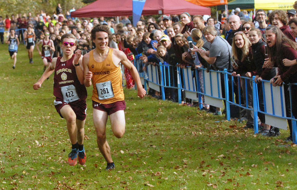Dimond's Noah Rygh, right, outraces Grace Christian's Aiden Zingone to the finish line in the boys junior varsity race Saturday during the New Balance XC Classic cross country running races at Russian Jack Springs Park. (Matt Tunseth / ADN)