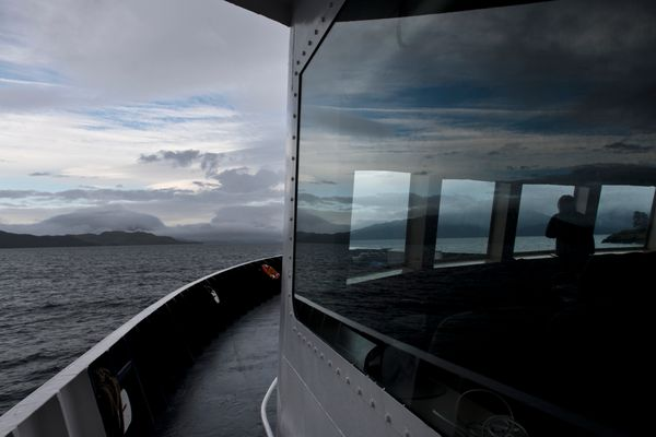 A passenger looks out the windows of the lounge of the Alaska Marine Highway ferry Aurora as it travels from Cordova to Whittier on September 18, 2019. (Marc Lester / ADN)