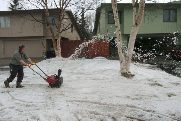 Mike Citro clears snow from the front lawn of his East Anchorage home on Tuesday, April 24, 2007. He also wanted to use up the gas in both of his snowblowers and is ready to get out the lawn mower. (Bill Roth/Anchorage Daily News)