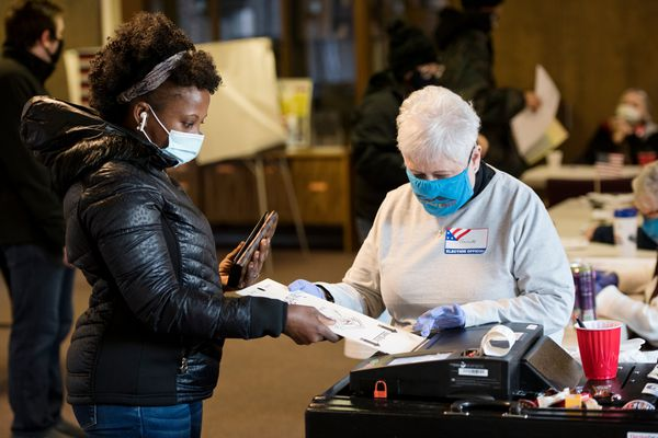 Jonsaba Joof, left, casts her ballot with help from election worker Annette Compton at Zion Lutheran Church on Boniface Parkway on November 3, 2020. (Marc Lester / ADN)