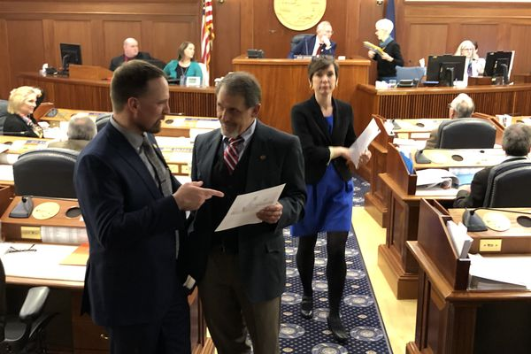 Rep. Ben Carpenter, R-Nikiski, talks to Rep. George Rauscher, R-Sutton, before the final vote on the state's supplemental budget on Wednesday, March 25, 2020. At background is Rep. Ivy Spohnholz, D-Anchorage. (James Brooks / ADN)