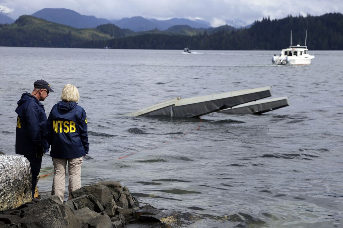 In this photo provided by the National Transportation Safety Board, NTSB investigator Clint Crookshanks, left, and member Jennifer Homendy stand near the site of some of the wreckage of the DHC-2 Beaver, Wednesday, May 15, 2019, that was involved in a midair collision near Ketchikan, Alaska, a couple of days earlier. (Peter Knudson/NTSB via AP)