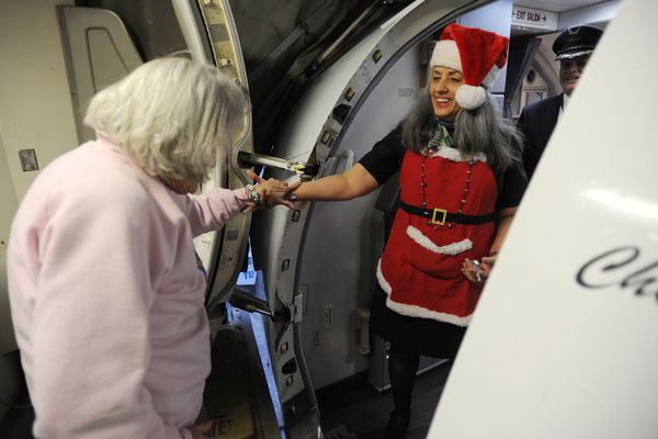 Virgina Cook gets help boarding the plane from Alaska Airlines flight attendant Lilly White on Christmas, Monday, Dec. 25, 2017. (Bill Roth / ADN)