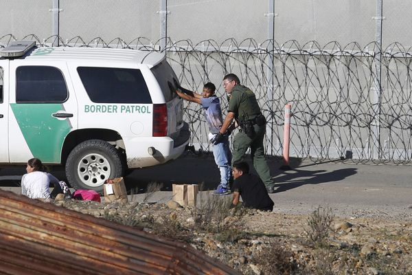 FILE - In this Dec. 15, 2018, file photo, Honduran asylum seekers are taken into custody by U.S. Border Patrol agents after the group crossed the U.S. border wall into San Diego, Calif., seen from Tijuana, Mexico. Detained asylum seekers who have shown they have a credible fear of returning to their country will no longer be able to ask a judge to grant them bond. U.S. Attorney General William Barr decided Tuesday, April 16, 2019, that asylum seekers who clear a