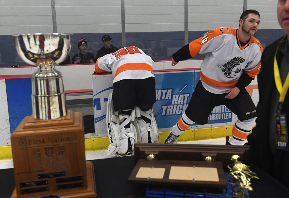 West High goalie Will Simpson is overcome with emotion as teammate Gunner Hanson skates away and the championship trophy is brought onto the ice. (Photo by Bob Hallinen)