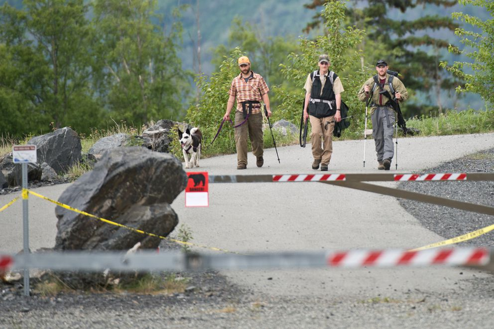 From left, Karelian bear dog handler Nils Pedersen, Fish and Game area biologist Dave Battle, and assistant area biologist Cory Stantorf return to the Bird Creek parking lot June 19 after searching for a black bear involved in a fatal mauling. (Marc Lester / Alaska Dispatch News)