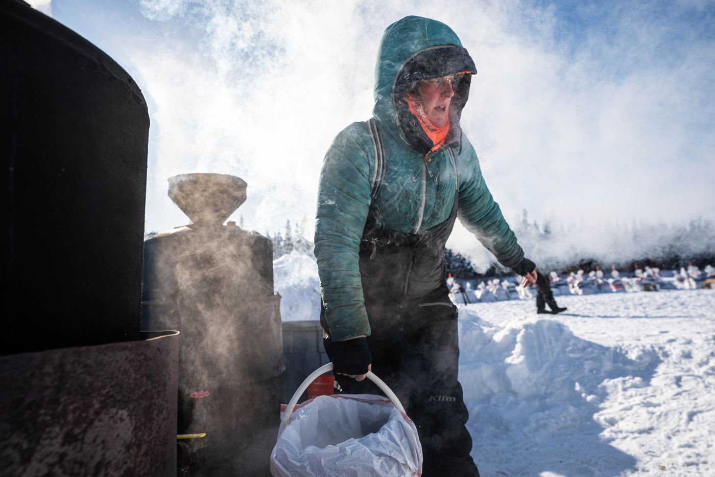 Paige Drobny carries hot water for her team after arriving in Nikolai. (Loren Holmes / ADN)