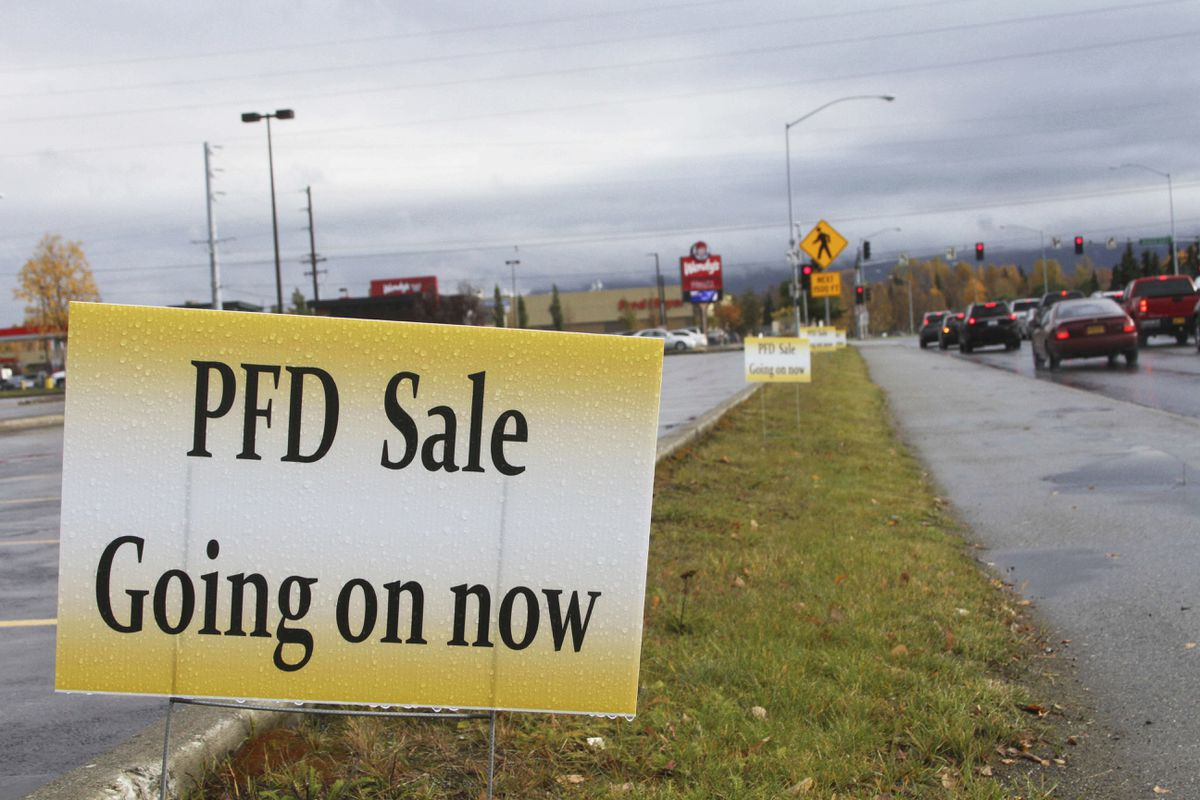 A sign meant to entice PFD recipients advertises a sale in Midtown Anchorage onOct. 4, 2017. (AP Photo/Mark Thiessen)