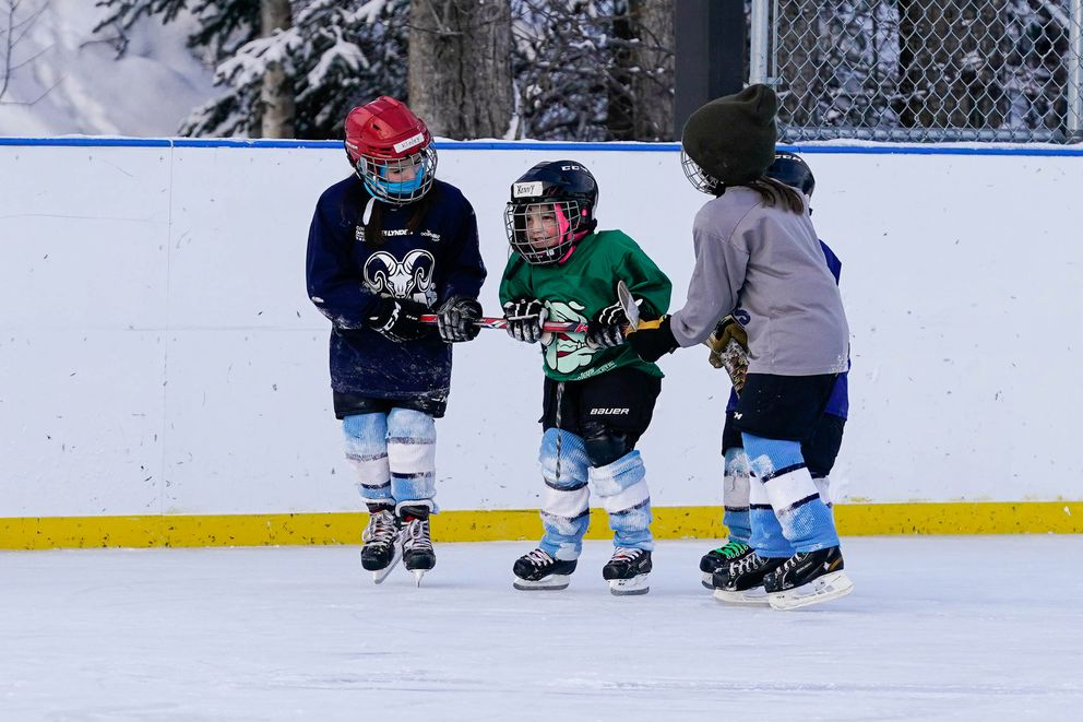 Kendall Greig, 4, gets help ice skating during a hockey practice at Tikishla Park on Saturday, Feb. 6, 2021. (Loren Holmes / ADN)