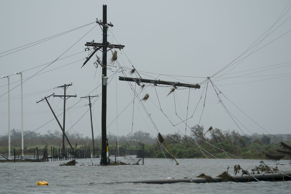 Floodwaters cover the street under downed utility wires Friday, Aug. 28, 2020, in Cameron, La., after Hurricane Laura moved through the area Thursday. (AP Photo/David J. Phillip)