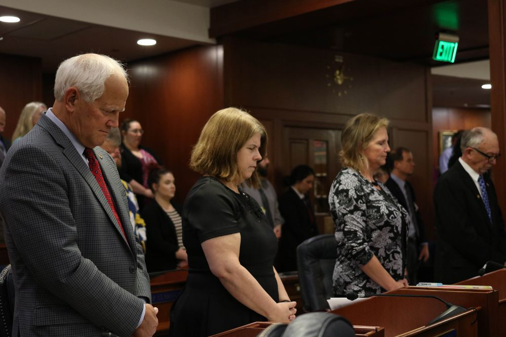 Alaska House members bow their heads during the ceremonies opening the Legislature's annual session January 16, 2018, at the Capitol in Juneau. From left, Republican Reps. Chris Birch of Anchorage, Tammie Wilson of North Pole, DeLena Johnson of Palmer and Steve Thompson of Fairbanks. (Nathaniel Herz / ADN)