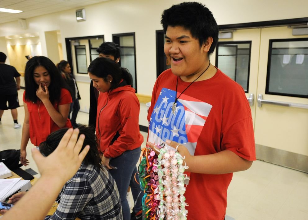 West High Poly Club president James Tuiniua, a junior, holds candy leis that students plan to sell as a fundraiser for the club. (Bill Roth / Alaska Dispatch News)