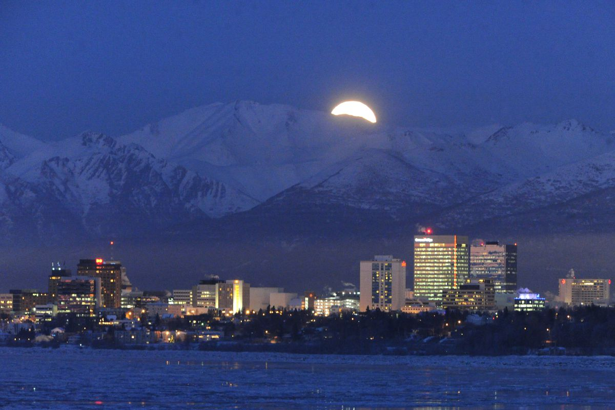 A full moon rises above the Chugach Mountains and the Anchorage skyline on Tuesday, Feb. 3, 2015.