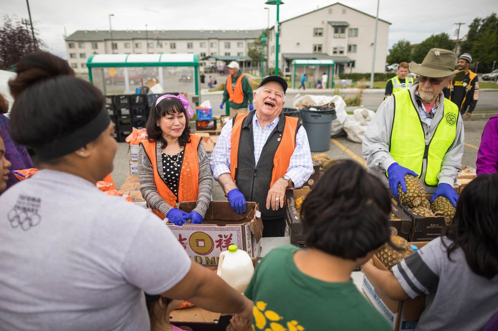 Yen Xuan Seymour, left, and Jack Seymour help hand out food at the Mobile Food Pantry. (Loren Holmes / Alaska Dispatch News)