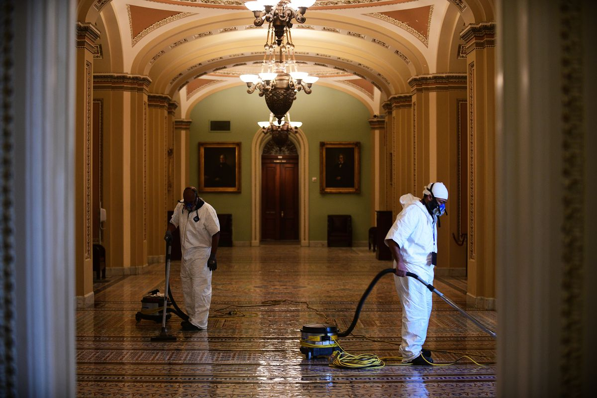 Workers clean the inside of the Capitol building one day after it was stormed, invaded and vandalized by rioters. Photo for The Washington Post by Astrid Riecken