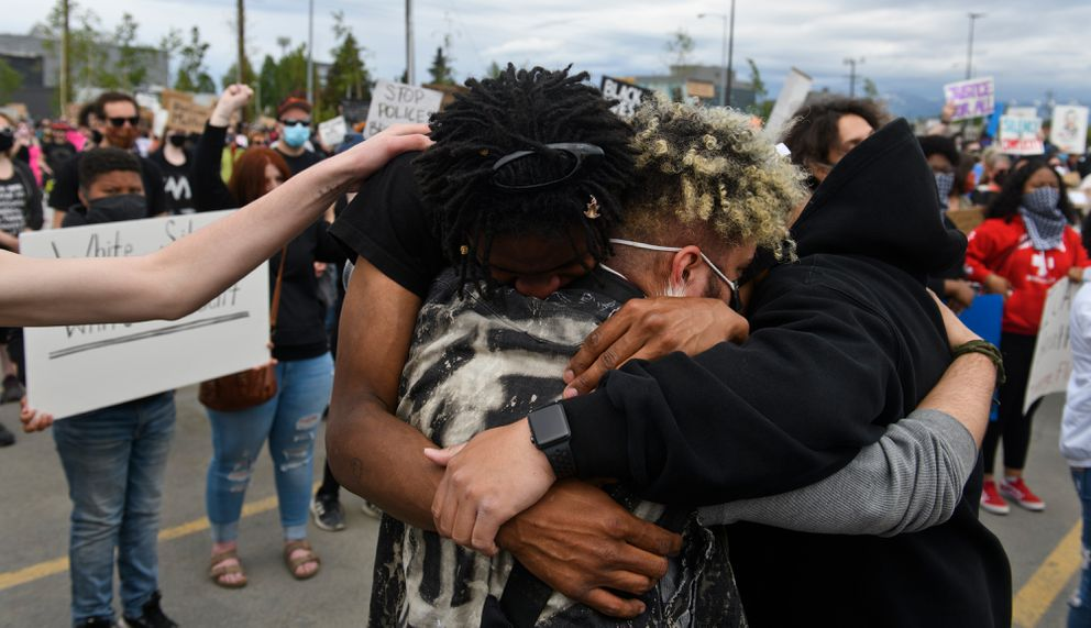 Men hug at the Midtown Mall rally. (Marc Lester / Anchorage Daily News)