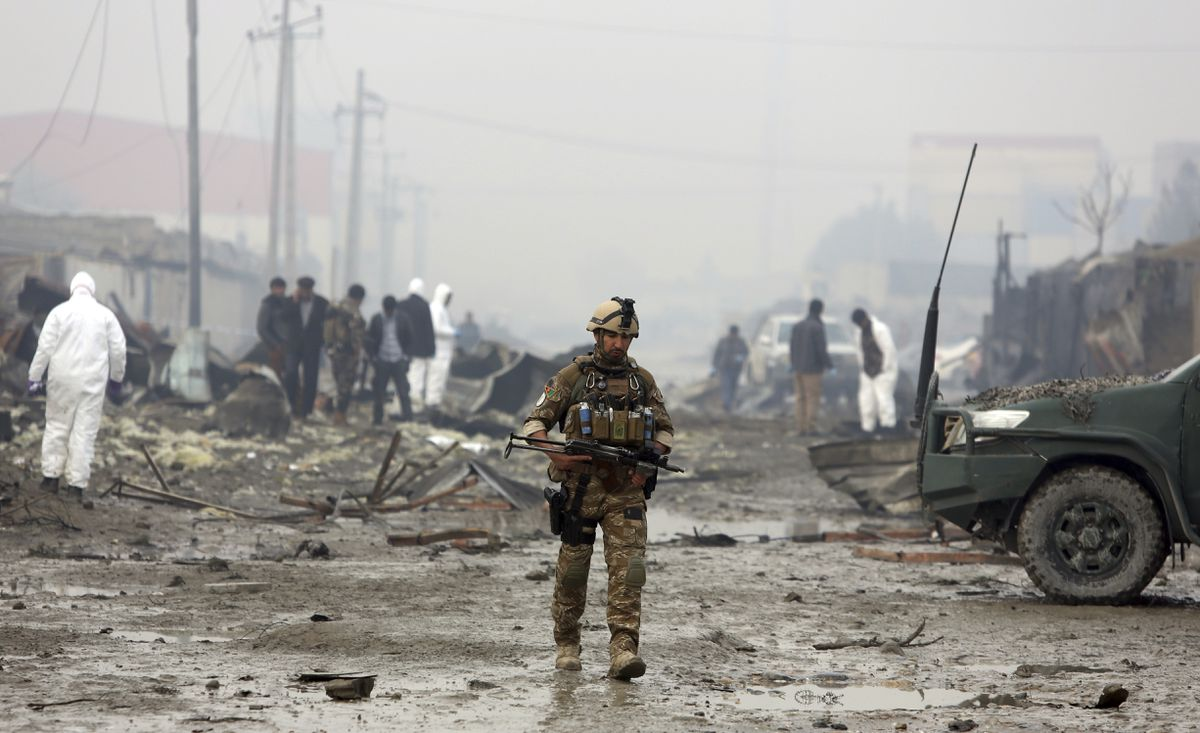 An Afghan security force walks around the site of suicide bomb attack in Kabul, Afghanistan, Thursday, Nov. 29, 2018. Taliban insurgents staged a coordinated attack targeting a security firm in the Afghan capital on Wednesday, killing people and wounding others. (AP Photo/Rahmat Gul)