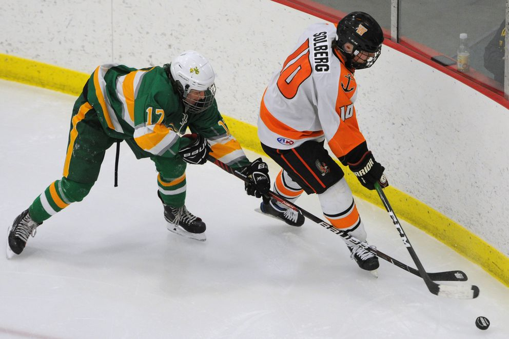 Service senior defenseman Patrick Clay and West senior Chase Solberg battle for control of the puck. (Bill Roth / ADN)