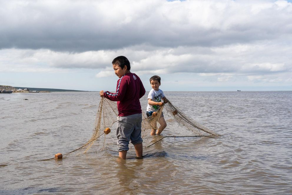 Drake Charles and Jeffrey Charles Jr. catch fish along the banks of the Baird Inlet in Mertarvik, Alaska, on July 15, 2020. (KATIE BASILE / KYUK)