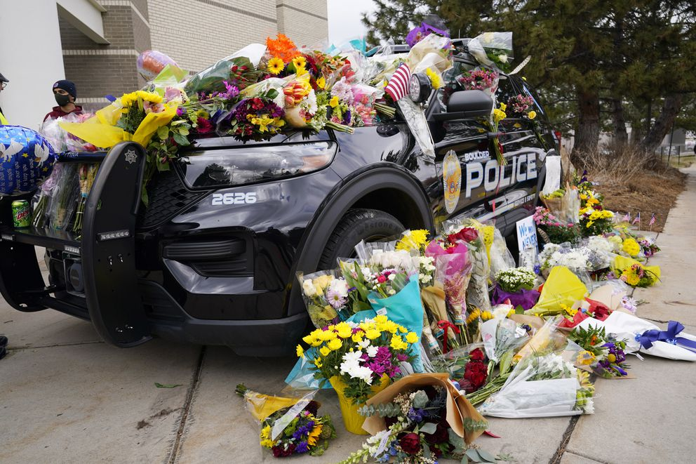 Police cruiser parked outside Boulder Police Department is covered with bouquets in tribute after an officer was one of the victims of a mass shooting at a King Soopers grocery store Tuesday, March 23, 2021, in Boulder, Colo. (AP Photo/David Zalubowski)