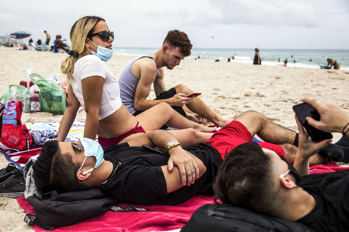 In the city of Miami Beach, Daniel Milian, from right, Miguel Martinez and Laura De Armas relax by the sea in South Beach on Friday with varying mask use. Whether to wear a mask in public has become fiercely controversial. Photo by Scott McIntyre for The Washington Post