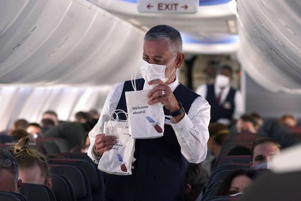 An American Airlines flight attendant hands out snack bags aboard a Boeing 737 Max jet before taking off from Dallas Fort Worth airport in Grapevine, Texas, Wednesday, Dec. 2, 2020. (AP Photo/LM Otero)