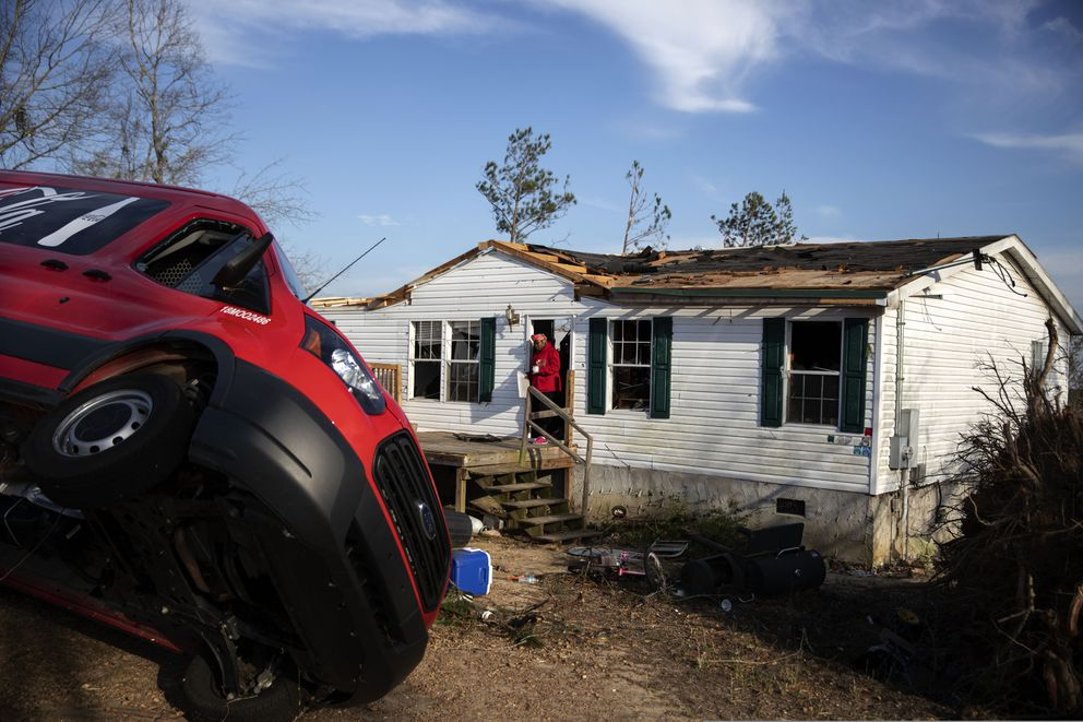 Kiara Slater carries out personal items from her parents' damaged home where they survived a tornado a day earlier in Beauregard, Ala., Monday, March 4, 2019. (AP Photo/David Goldman)