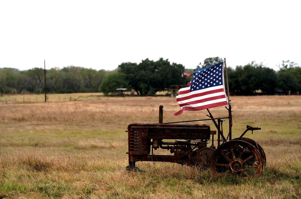 A tattered U.S. flag flies on an old tractor in a field outside Sutherland Springs, near the site of the shooting at the First Baptist Church. REUTERS/Rick Wilking