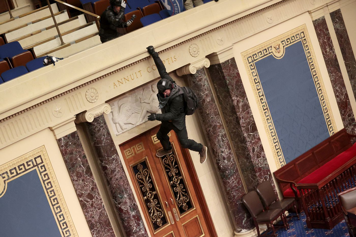 A protester is seen hanging from the balcony in the Senate Chamber on Wednesday, Jan. 6, 2021 in Washington, D.C. (Win McNamee/Getty Images/TNS)