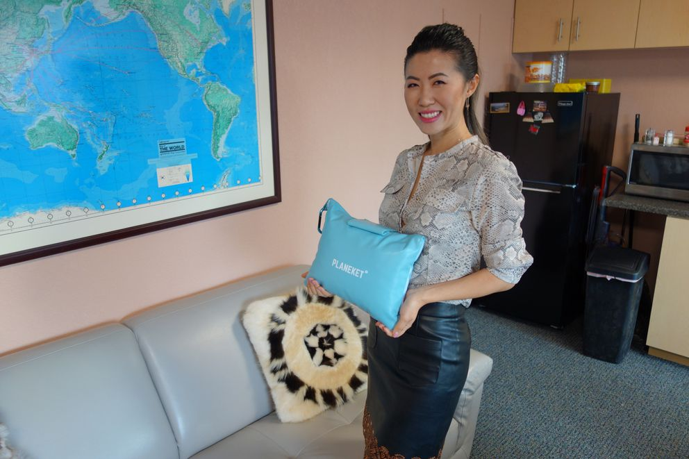 Jin Chen stands with the first Planeket travel kit, which she developed in Anchorage. (Photo by Scott McMurren)