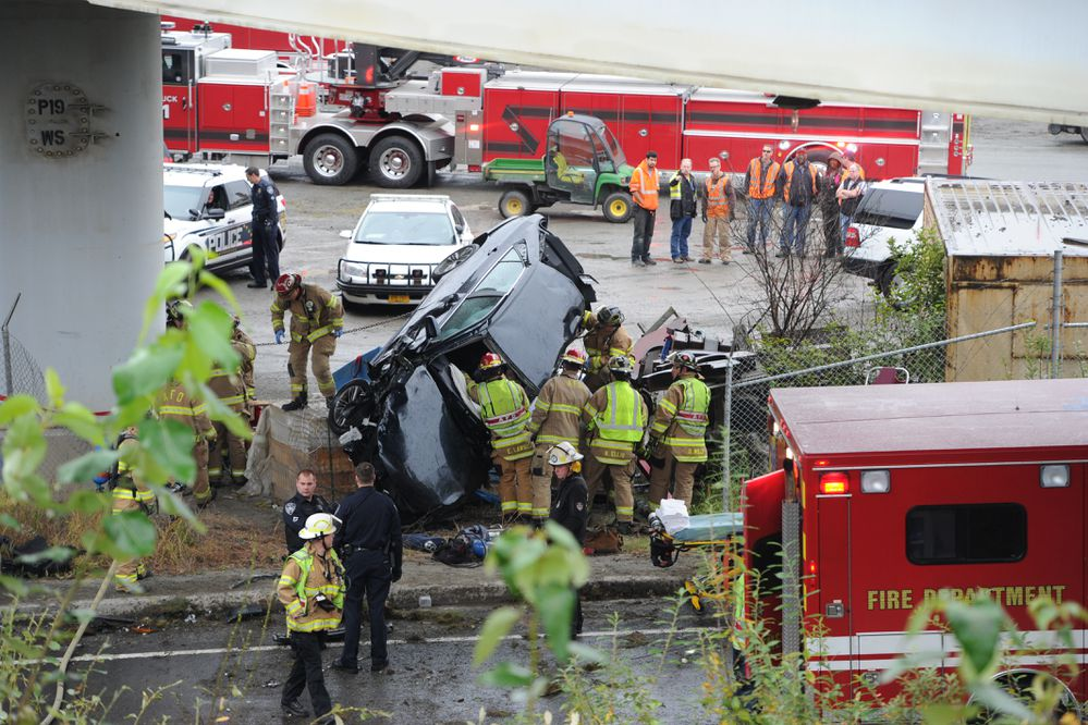 Anchorage firefighters extricate a woman from a vehicle after a collision sent her over an embankment under the that on Thursday morning, Sept. 21, 2017. (Bill Roth / Alaska Dispatch News)