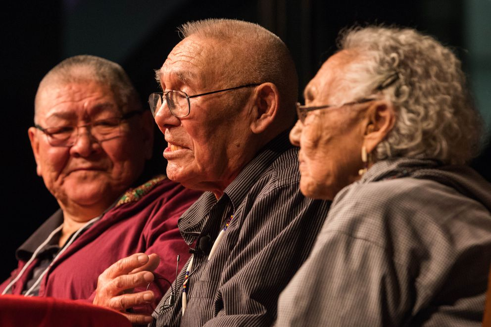 Mark John, left, translates for Elders and Youth keynote speakers Raphael and Vivian Jimmy during the elders keynote address at the Carlson Center in Fairbanks on Tuesday. The Jimmys have been married nearly 70 years. (Loren Holmes / Alaska Dispatch News)