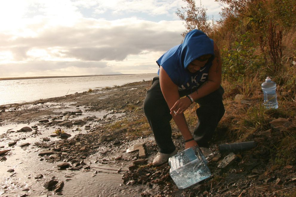 Trey Sisk, basketball and wrestling coach at Mountain Village High School, gathers spring water from a source that flows from Azachorok Hill into the Yukon River. (Lisa Demer / Alaska Dispatch News)
