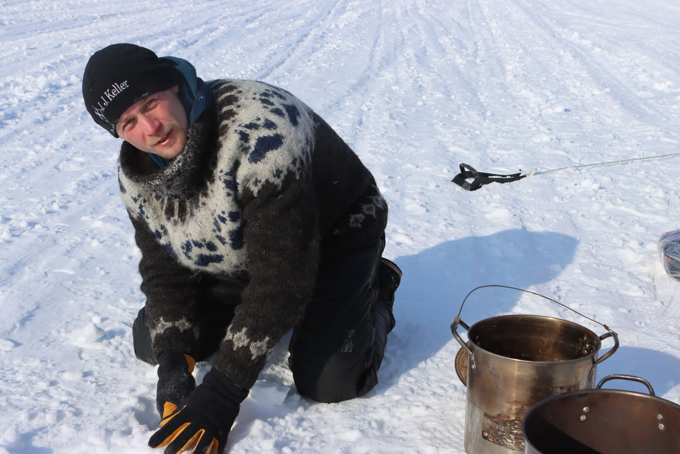 Dallas Seavey uses a knife to cut blocks of snow to melt in his cooker feeding his dogs during a rest break at the Iditarod checkpoint on Thursday. (Zachariah Hughes/for ADN)
